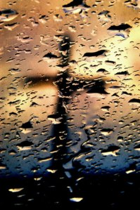 Cross through rainy glass