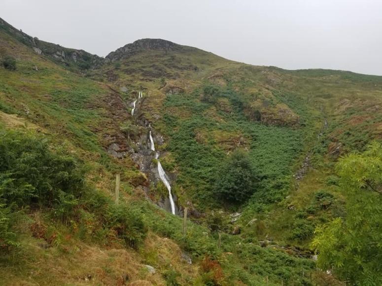 Slender set of waterfalls tumbling down a rocky green hillside