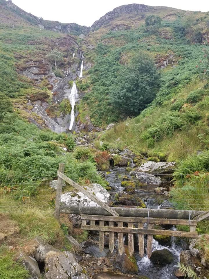 Small set of waterfalls tumbling down an open rocky hillside
