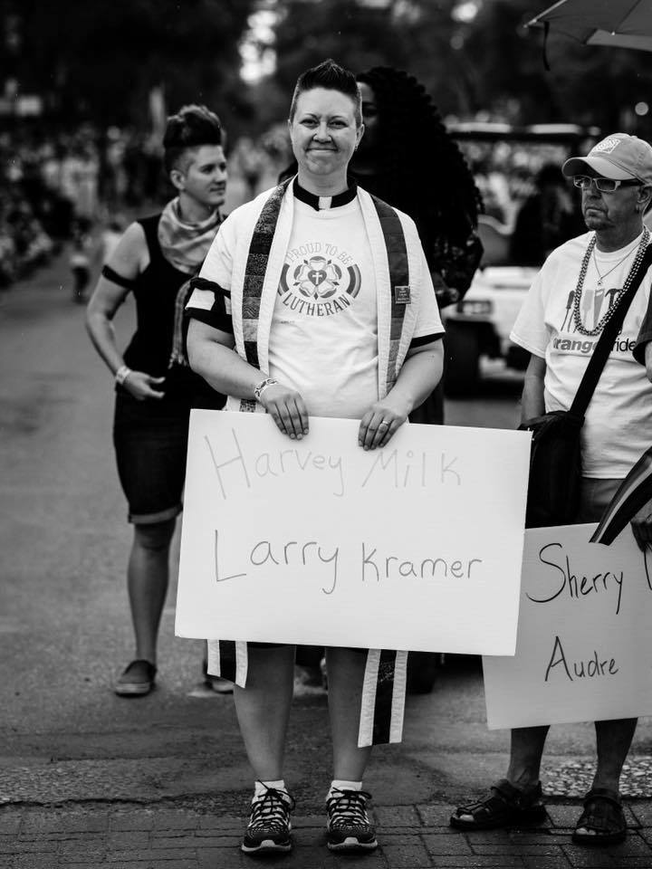 """Black and white photo of a trans/genderqueer person at a Pride parade holding a sign reading """"Harvey Milk, Larry Kramer""""."""