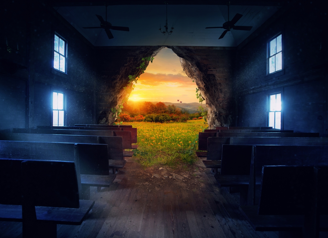 Old darkened country church with large hole in front wall surrounded by vines; beautiful pasture at sunset waits outside; light comes in