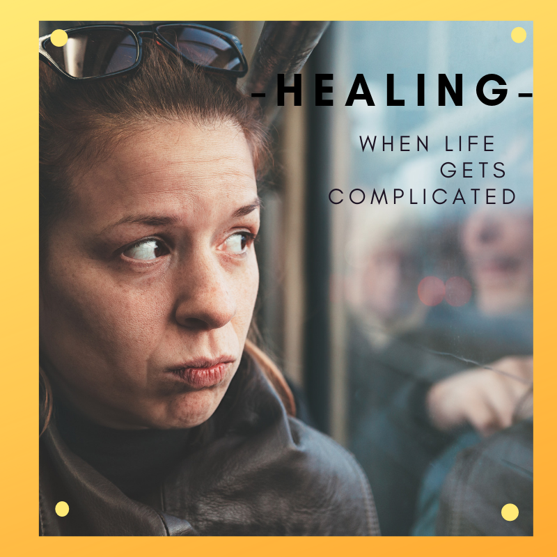"Woman with sunglasses pushed back on her head staring at her reflection in a bus window. Text reads: ""Healing: When Life Gets Complicated."""