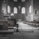 Man with white hair and black leather jacket sitting in wooden pew facing the front of an old stone church, cross hanging high over the altar. Caption reads: Where is Jesus now?